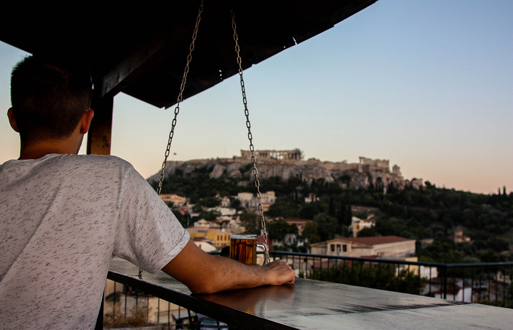 The great atmosphere, other travelers and the view to Acropolis is what you will feel at Pella Inn's Rooftop Bar.